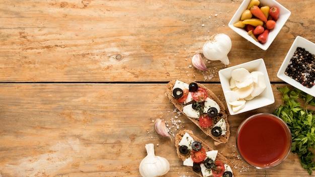 Vista dell'angolo alto della bruschetta e dell'ingrediente su fondo di legno Foto Gratuite
