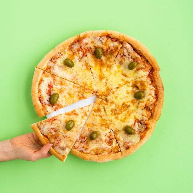 Vista dell'angolo alto della fetta femminile della pizza della tenuta della mano sopra fondo verde Foto Gratuite