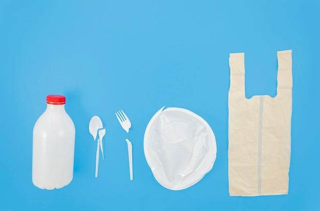 Vista dell'angolo alto della fila di immondizia di plastica sopra fondo blu Foto Gratuite