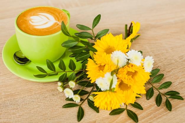 Vista dell'angolo alto della tazza di caffè di arte del latte con il fiore fresco sopra il contesto strutturato di legno Foto Gratuite