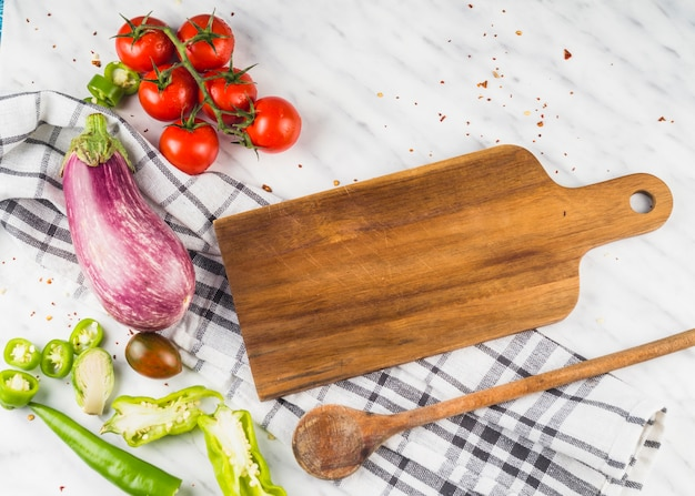 Vista dell'angolo alto della verdura sana con la siviera di legno ed il bordo di cottura in cucina Foto Gratuite