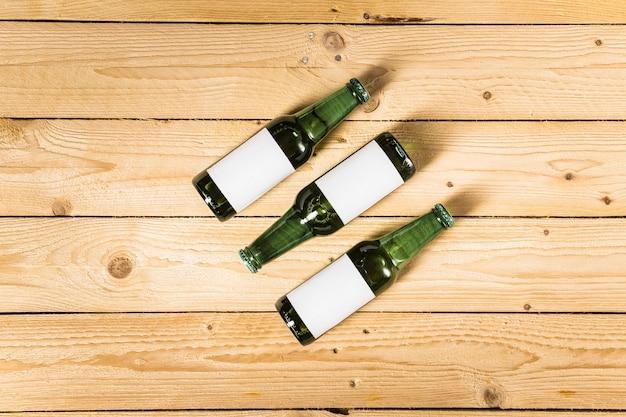 Vista dell'angolo alto delle bottiglie alcoliche su superficie di legno Foto Gratuite