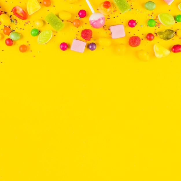 Vista dell'angolo alto delle caramelle dolci su fondo giallo Foto Gratuite