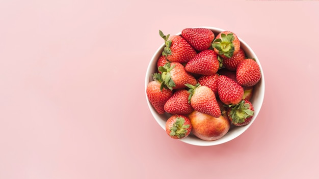 Vista dell'angolo alto delle fragole e delle mele fresche in ciotola su fondo rosa Foto Gratuite