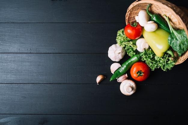Vista dell'angolo alto delle verdure crude con il canestro di vimini su superficie di legno nera Foto Gratuite