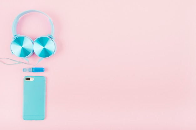 Vista dell'angolo alto dello smartphone e della cuffia sul contesto rosa Foto Gratuite