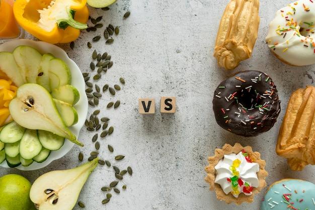 Vista dell'angolo alto di alimento saporito che mostra concetto sano contro non sano Foto Gratuite