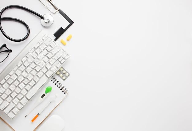 Vista dell'angolo alto di attrezzatura medica e della tastiera senza fili sopra il contesto Foto Gratuite