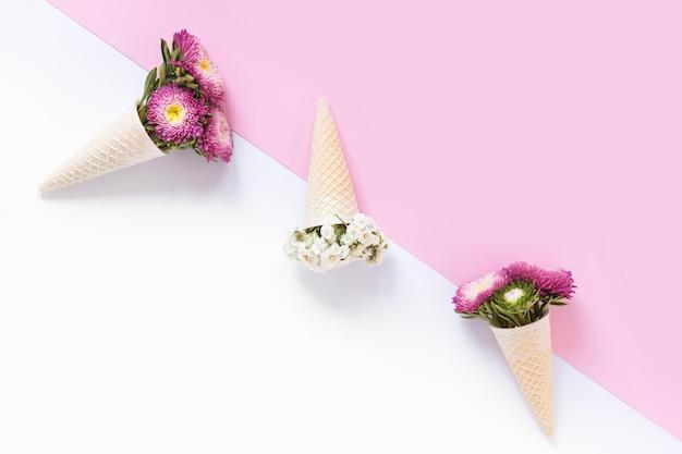 Vista dell'angolo alto di bei fiori nel cono gelato della cialda su doppio fondo Foto Gratuite