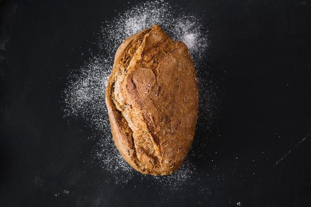 Vista dell'angolo alto di pane di recente cotto su fondo nero Foto Gratuite