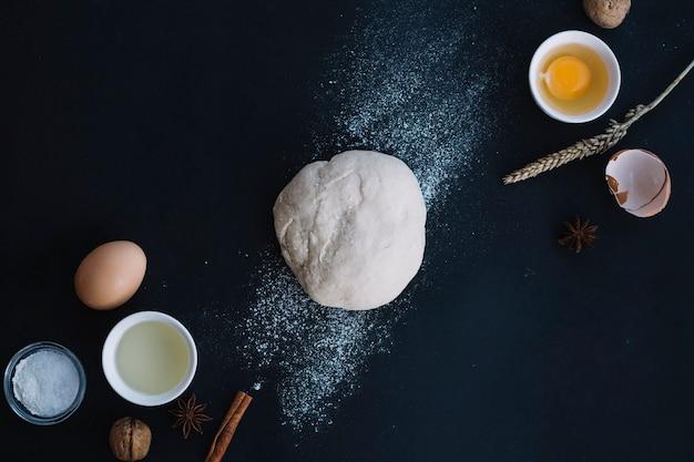 Vista dell'angolo alto di pasta con gli ingredienti di cottura sul contesto nero Foto Gratuite
