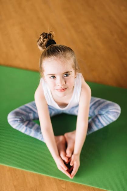 Vista dell'angolo alto di piccola ragazza che si esercita sulla stuoia verde Foto Gratuite