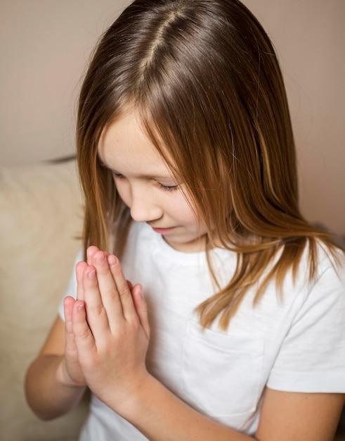 Vista dell'angolo alto di pregare della bambina Foto Gratuite