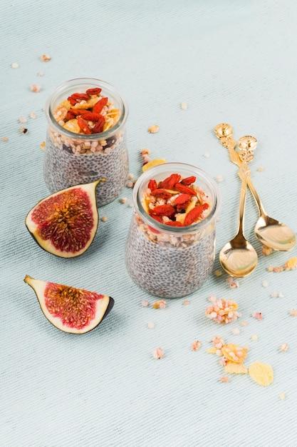 Vista dell'angolo alto di un budino dei semi di chia di due vasi; cucchiaio di colore dorato e fette di fico su sfondo colorato Foto Gratuite