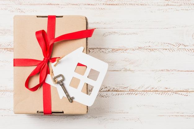 Vista dell'angolo alto di un contenitore di regalo legato con il nastro rosso sulla chiave della casa sopra la tavola di legno Foto Gratuite