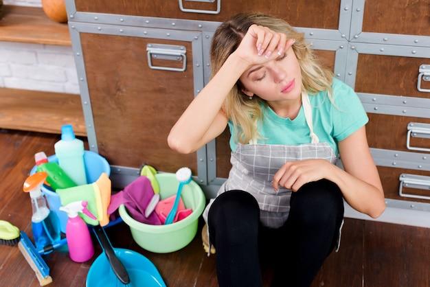 Vista dell'angolo alto di una donna delle pulizie sovraccarica che si siede sul pavimento con gli strumenti e i prodotti di pulizia Foto Gratuite