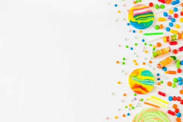 Vista dell'angolo alto di varie caramelle variopinte su superficie bianca Foto Gratuite