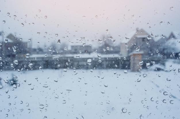 Vista delle case attraverso una finestra con gocce di pioggia Foto Premium