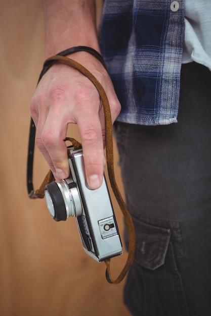 Vista delle mani maschili che tengono una retro macchina fotografica Foto Premium