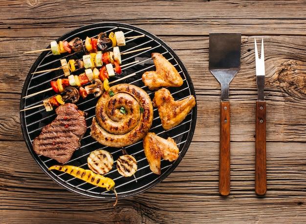 Vista di alto angolo di deliziose grigliate di carne con verdure oltre i carboni su un barbecue Foto Gratuite