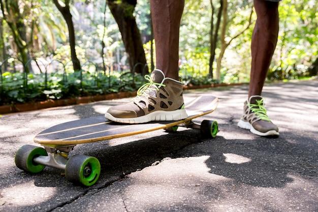 Vista di angolo basso dei piedi di un giovane skateboarder maschio in scarpe da ginnastica al parco Foto Gratuite