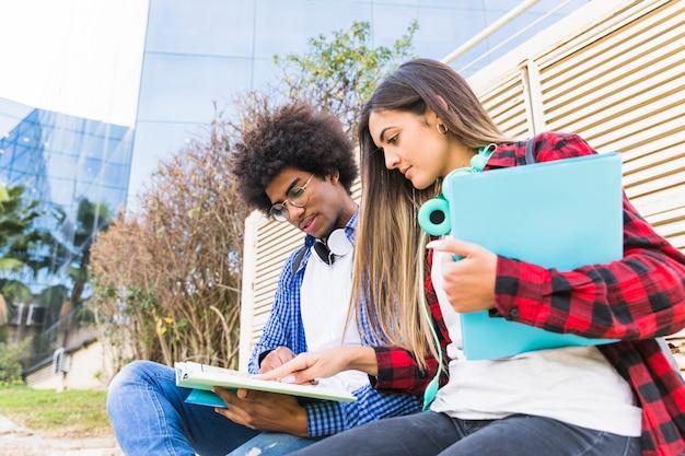 Vista di angolo basso di giovani studenti diversi che studiano insieme davanti all'edificio universitario Foto Gratuite
