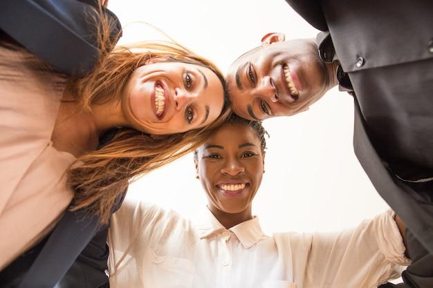 Vista di angolo basso di tre che abbracciano i colleghi multietnici felici Foto Gratuite