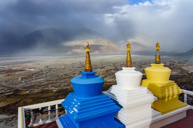 Vista di tre stupa con la valle di nubra sullo sfondo dal monastero di diskit in ladakh, in india. Foto Premium