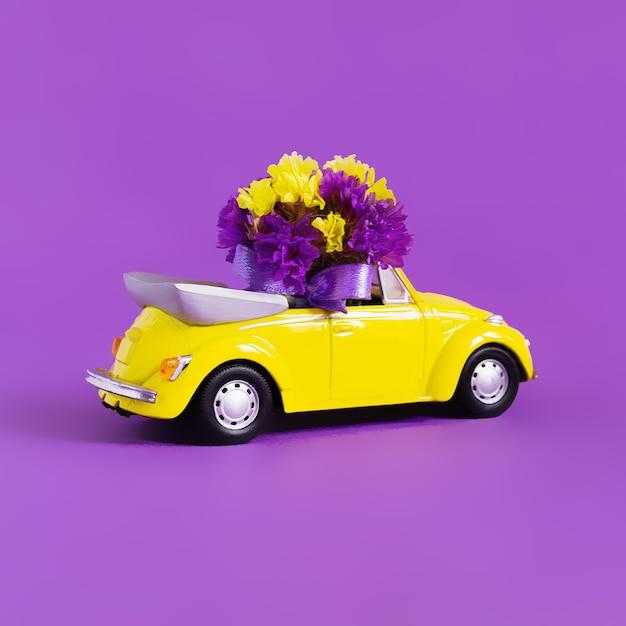 Vista di un'automobile convertibile gialla variopinta con un mazzo di fiori su un rosa che lascia la nuvola blu sotto forma di cuore. concetto di vacanza, consegna, arte, trasporto Foto Premium