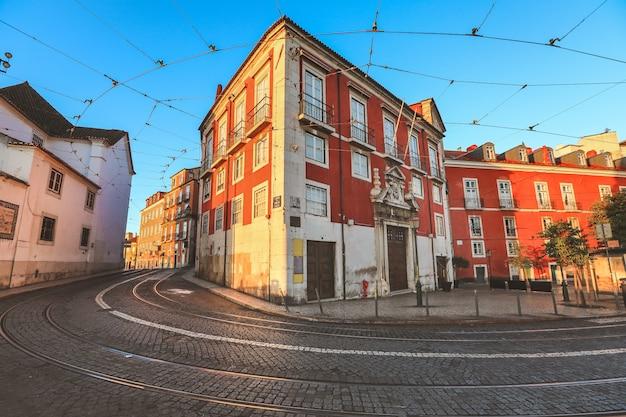 Vista di vecchia via tradizionale e costruzioni variopinte di mattina con le piste del tram a lisbona. Foto Premium
