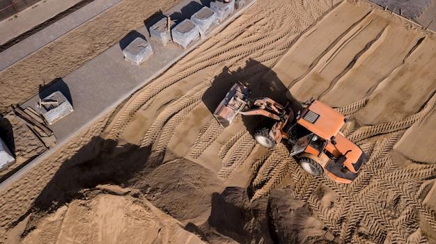 Vista drone di camion, escavatori e lavori di riparazione della strada nel paesaggio rurale. fotografia di droni. Foto Premium