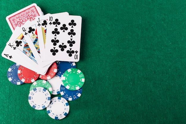 Vista elevata dei club e dei chip del royal flush sul tavolo da poker verde Foto Gratuite