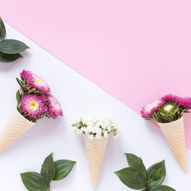 Vista elevata dei fiori freschi nel cono gelato della cialda sul doppio contesto Foto Gratuite