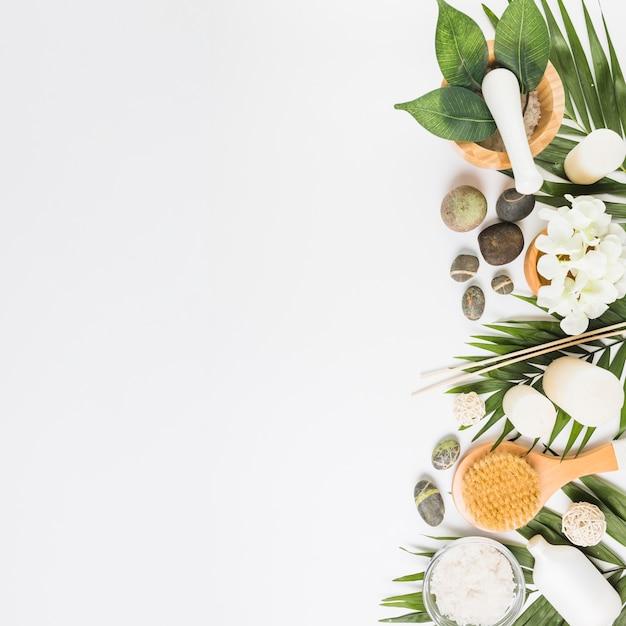 Vista elevata dei fiori; pietre spa; le foglie; pennello e candele su sfondo bianco Foto Gratuite