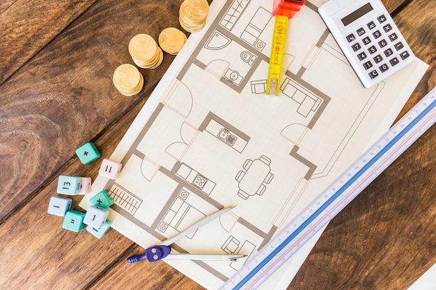Vista elevata del divisore, del righello, dei blocchi per la matematica, del calcolatore, delle monete impilate e del modello su fondo di legno Foto Gratuite