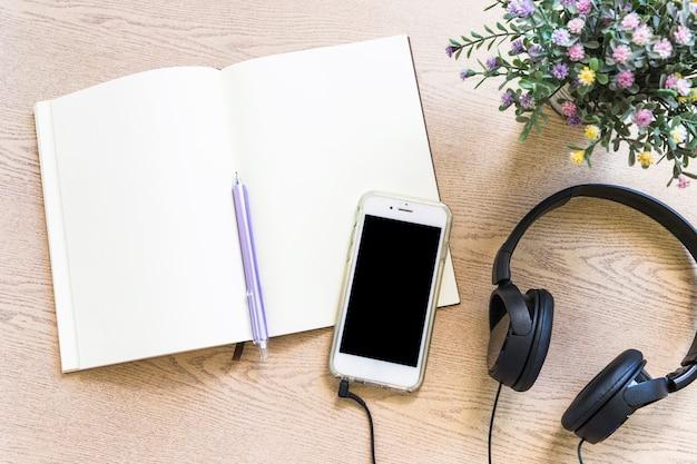 Vista elevata del libro bianco con penna; cellulare e auricolare sul tavolo di legno Foto Gratuite