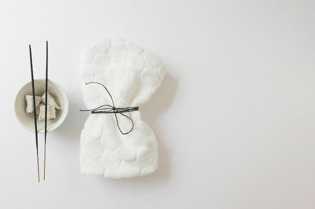 Vista elevata del tovagliolo legato; bastoncino di incenso e pietra pomice su superficie bianca Foto Gratuite