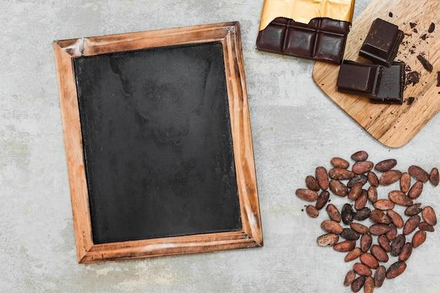 Vista elevata dell'ardesia di legno in bianco, della barra di cioccolato fondente e delle fave di cacao su fondo concreto Foto Gratuite