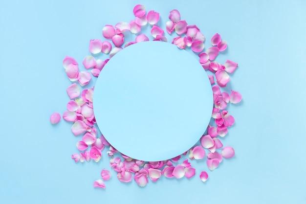 Vista elevata della cornice circolare circondata con petali di rosa rosa su sfondo blu Foto Gratuite
