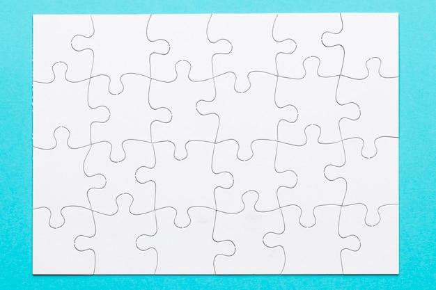 Vista elevata della griglia bianca del puzzle sulla superficie del blu Foto Gratuite