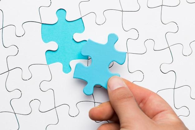 Vista elevata della mano che tiene il pezzo blu di puzzle sopra la priorità bassa bianca di puzzle Foto Gratuite