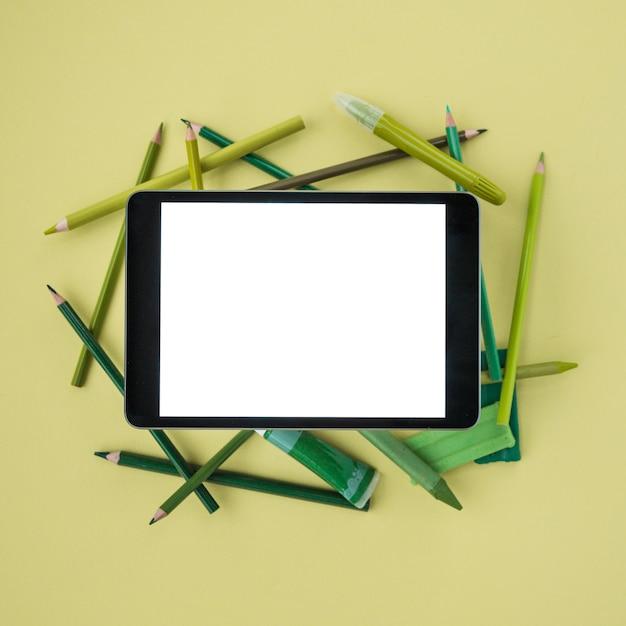Vista elevata della tavoletta digitale con schermo bianco sugli accessori di verniciatura sopra la superficie di tinta unita Foto Gratuite