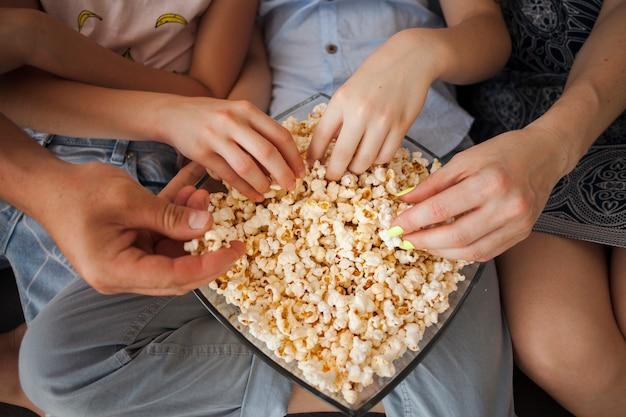 Vista elevata delle mani che tengono popcorn a casa Foto Gratuite
