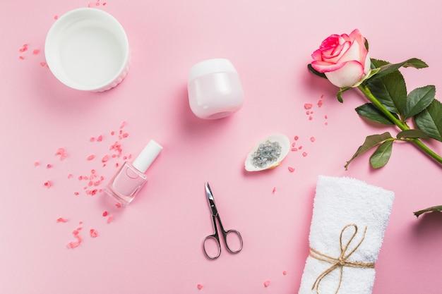 Vista elevata dello smalto per unghie; forbici; sale; asciugamano; fiori e crema idratante sulla superficie rosa Foto Gratuite