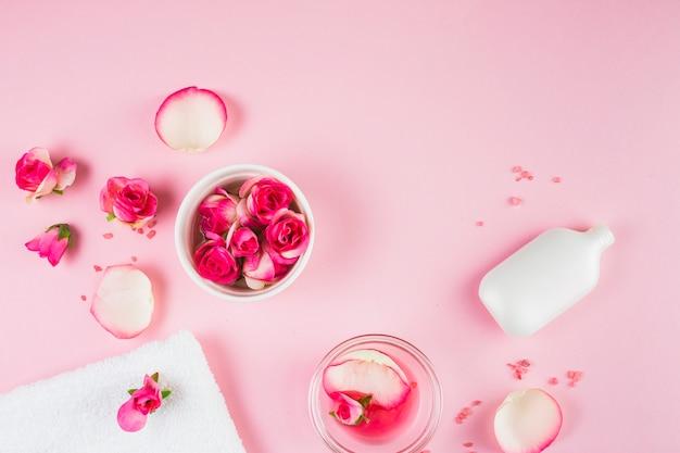 Vista elevata di asciugamano; fiori e bottiglia su sfondo rosa Foto Gratuite
