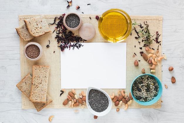 Vista elevata di carta bianca circondata da cibo sano sopra tovaglietta sul tavolo Foto Gratuite