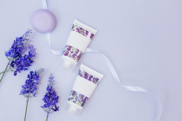 Vista elevata di fiori di lavanda finti; sapone; crema idratante e nastro Foto Gratuite