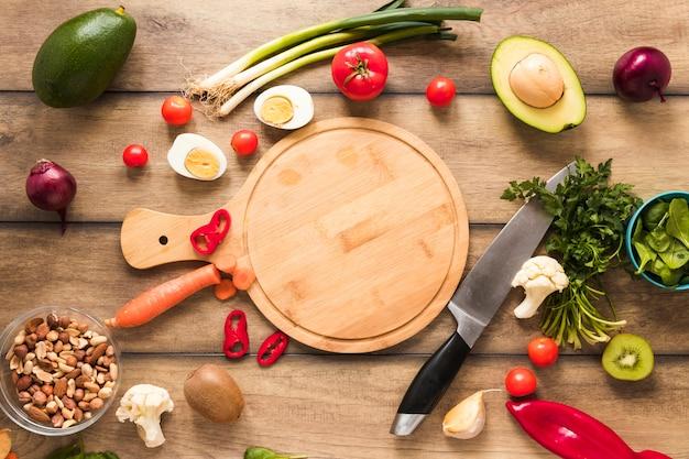 Vista elevata di ingredienti freschi; uovo; verdure e tagliere con coltello sul tavolo Foto Gratuite