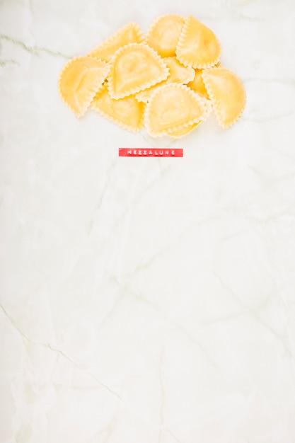 Vista elevata di pasta di mezzaluna su marmo Foto Gratuite