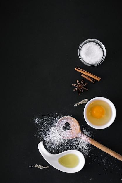 Vista elevata di petrolio; uovo; farina; zucchero; cereali; cucchiaio di legno di forma di cuore e spezie sulla superficie nera Foto Gratuite